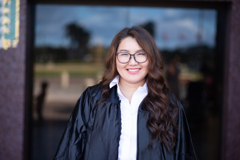 Otgontuya Lily Tumursukh smiling wearing glasses, a white shirt and a black graduation gown with a glass door behind her.