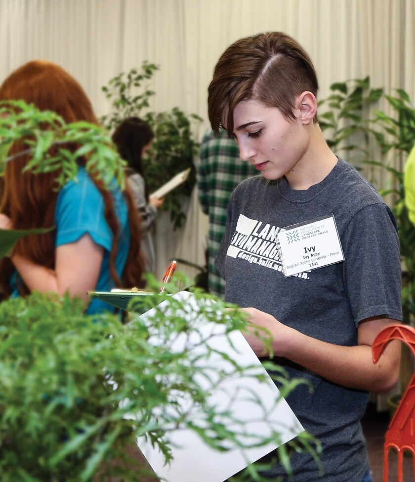 girl writing on clipboard by plants.jpg