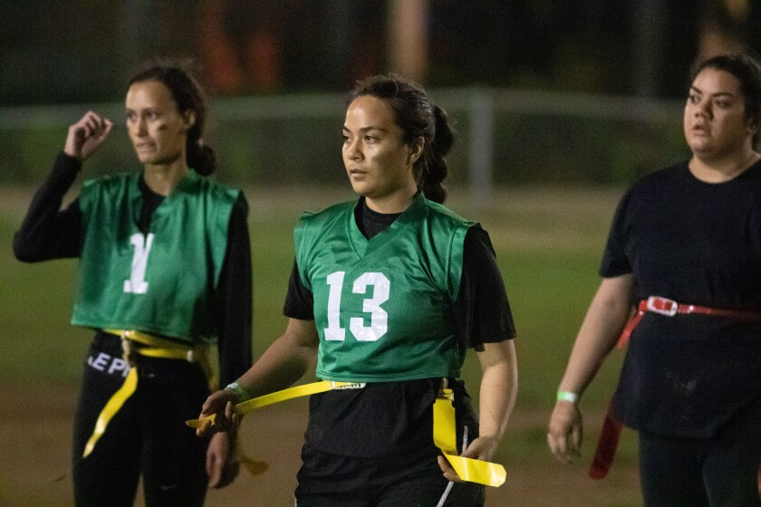 Female players hold their yellow flags on the Rugby Field at BYUH.