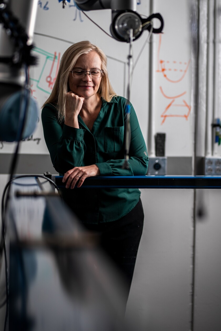 A professional portrait of Traci Neilsen, BYU astronomy and physics professor, in a lab.