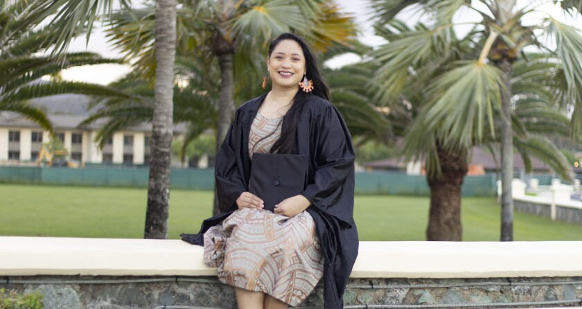 Hernaez sits on a stone wall with palms in the background smiling wearing a golden Polynesian designed dress, earrings and a black graduation gown.