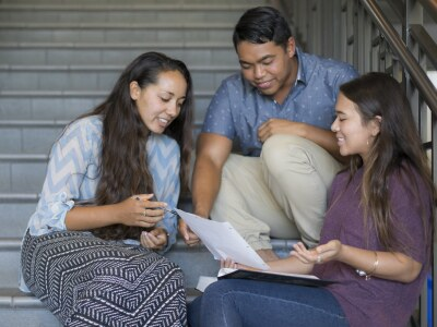 2 female students and 1 male student sitting on the stairs, discussing and looking at one sheet of paper.
