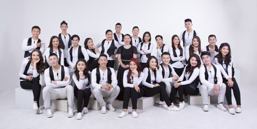 Over 20 men and women wearing white shirts, black vests and white and black pants sit and stand around eachother.