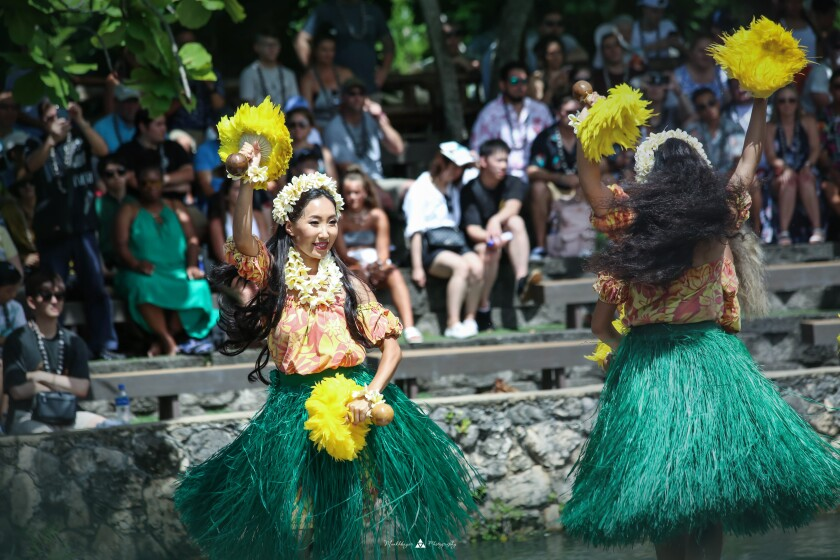 Ganzorigt dancing in a grass skirt, orange and yellow shirt and flower leis around her neck and head holding up wooden handles with yellow feathers on them with a crowd behind her.