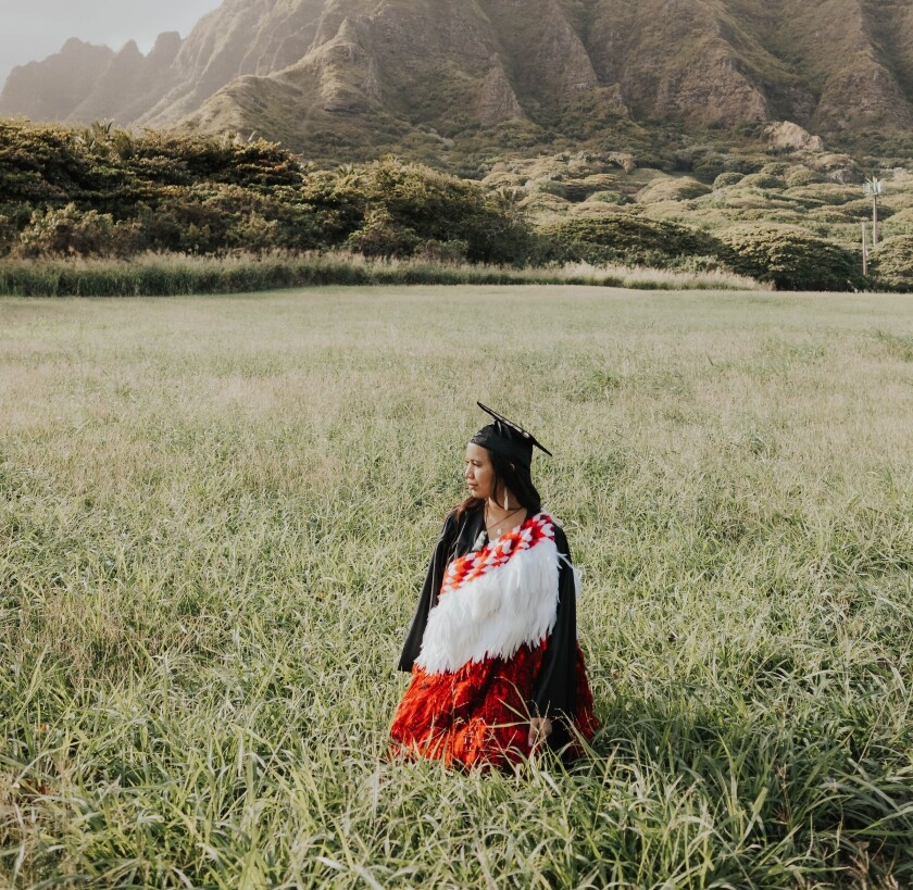 Mahe sits in a field with the mountains behind her wearing a red, white and orange feathered wrap around her black graduation cap and gown
