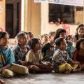Image of a group of elementary-age children sitting and learning