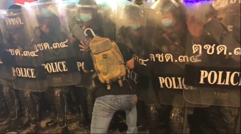A Thai protester pushes into riot police, 2020.