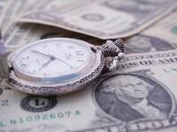 Pocket watch resting on dollar bills.