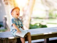 Image of little boy sitting and laughing with a book on his lap