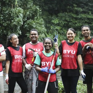 A group of students wearing BYU–Hawaii marked safety vests and holding gardening and landscaping tools