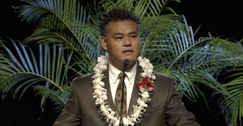 Dr. Ban Phung, wearing a lei, speaks at the podium in the Cannon Activities Center.