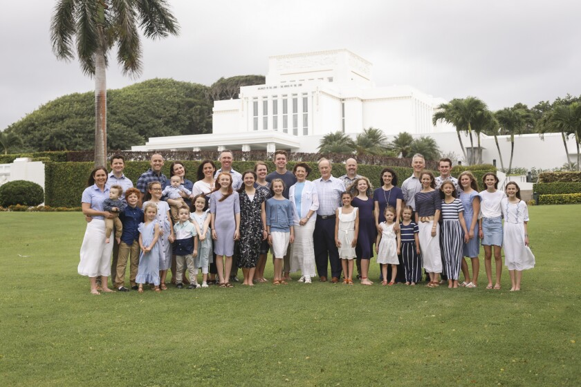 Susan and John Tanner stand in the middle with their children and grandchildren wearing dress clothes with the Laie Hawaii Temple in the background.