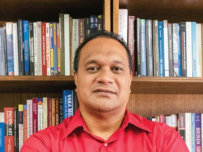 Tevita O. Ka'ili stands in front of a bookshelf wearing a red shirt