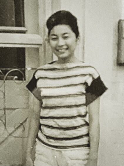 Jean Okimoto in a black and white photo from the late 1950s wearing a striped shirt and white pants standing by the front door of a house.