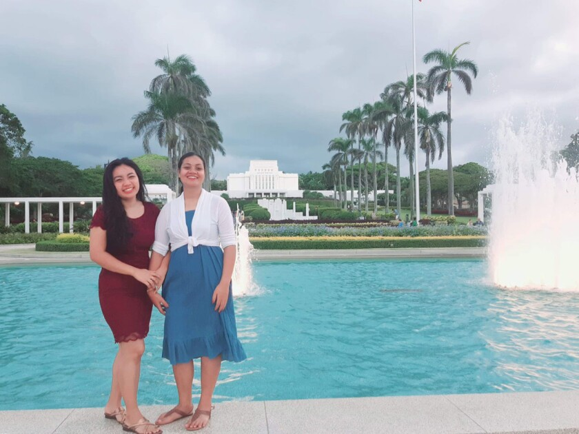 Shin (left) stands in a red dress beside Beia (right) wearing a blue dress with a white cardigan with a water fountain, palm trees and the Laie Hawaii Temple in the background.