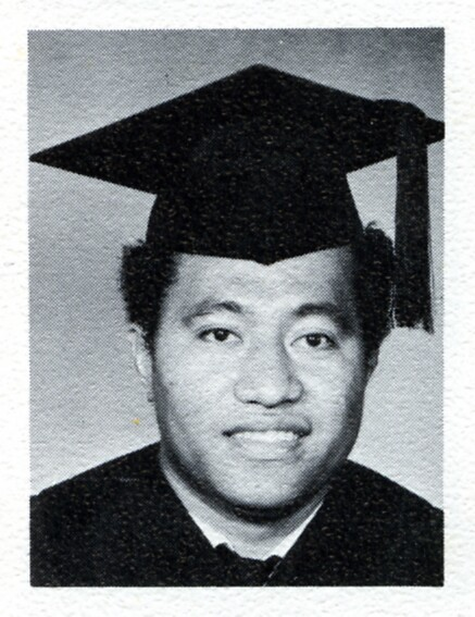 Ropeti Lesā in a black and white photo smiling wearing a cap and gown.