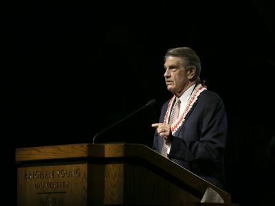 President Hallstrom wearing a dark suit and white and red poka dotted tie and white and red lei standing and speaking at a wooden podium with blackness behind him.