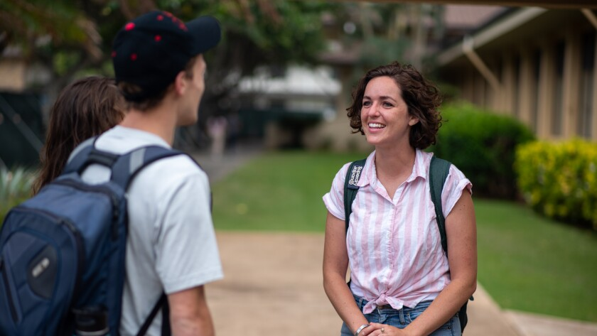 Nelson, wearing a pink and white striped button-up collared shirt and jeans, talking to two friends, a boy and a girl, on BYUH campus.