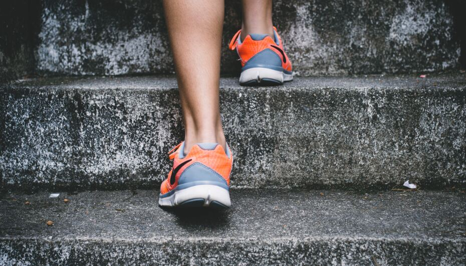 Image of feet in exercise shoes walking up concrete steps