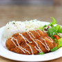 This is a photo of a lunch plate. Two pieces of deep fried fish, two scoops of rice, and salad are on the plate.