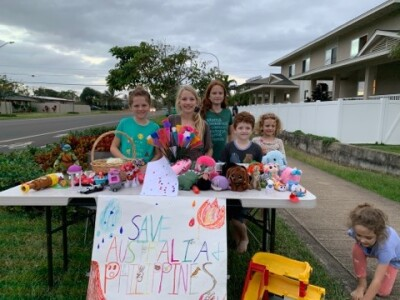 """A table set up on Kulanui Street in Laie has toys for sale by 6 kids with a sign that reads """"Save Australia + Philippines"""