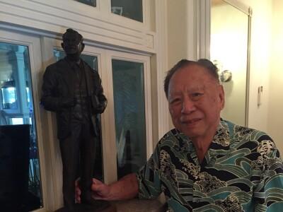 Photo of Lenard Fong standing by a miniature statue