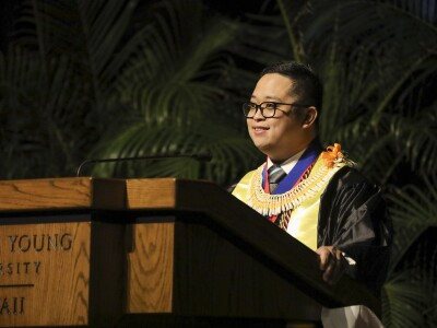 Terrence A. Dela Peña wearing graduation robes at a podium.