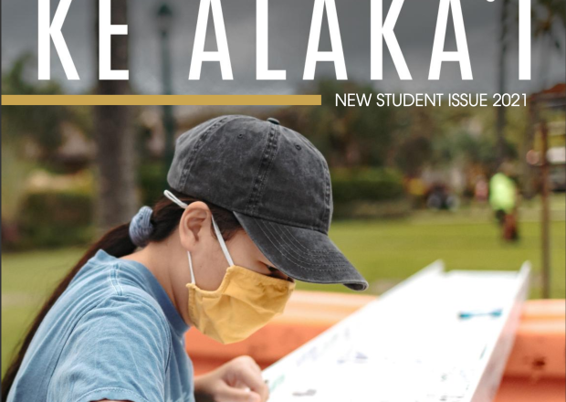 A student wearing a mask, grey baseball cap and blue short-sleeved T-shirt signs her name with a black permanent marker to an I-beam painted white. The I-beam was used to help build the new Science Building on campus and was signed by members of the BYU-Hawaii ohana.