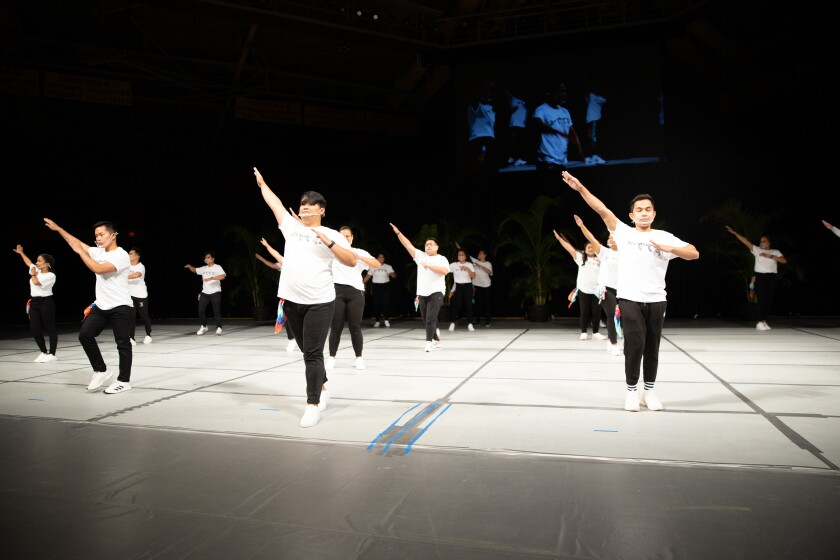 Dancers wearing white shirts and black pants hold up their arms slanted to the left on stage.