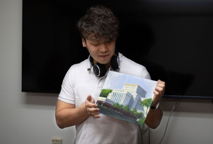 A man is holding a painting of the Laie Hawaii Temple