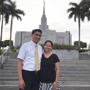 A portrait of David and May Villanueva smiling at the camera with stairs and a tall temple building in the background.