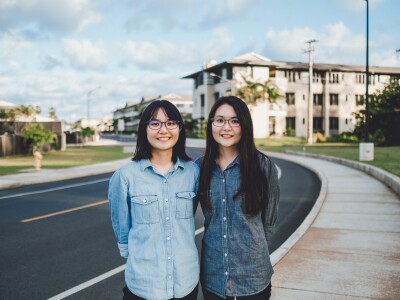 Twin sisters, the Oshiros, stand next to each other on campus near a street.