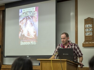 """Brandon Mull stands behind a computer at a podium. Behind him is a projector screen with a photo of his book """"Dragonwatch."""""""
