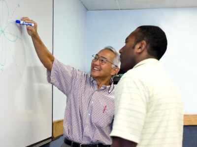 Image of instructor helping student in class