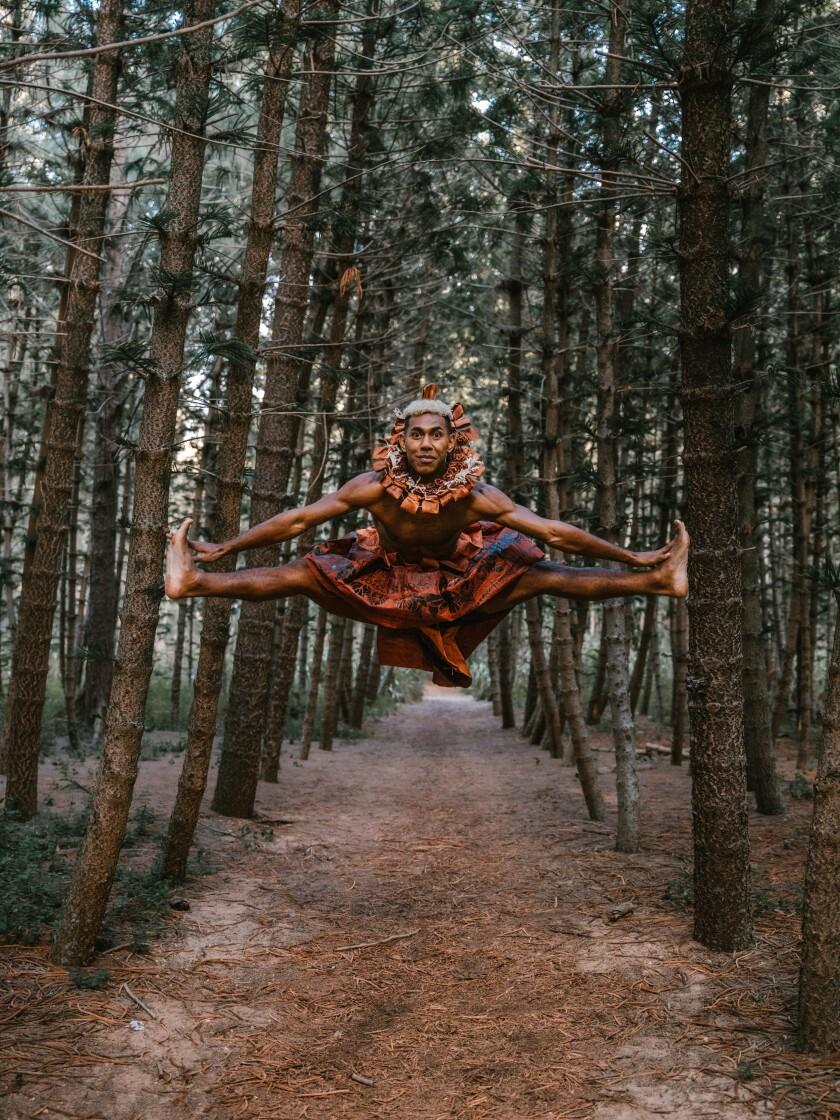 A guy in traditional Fijian dress jumps up, with his legs out to the sides and touches them with his hands on a path that leads through a forest of trees.