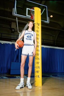 "Shawn Bradley measuring 7'6"" and holding a basketball"