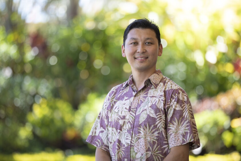 Tserennyam wearing an aloha style shirt smiling for the camera with greenery in the background.