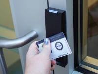 Hand scanning BYU ID on electronic door lock.