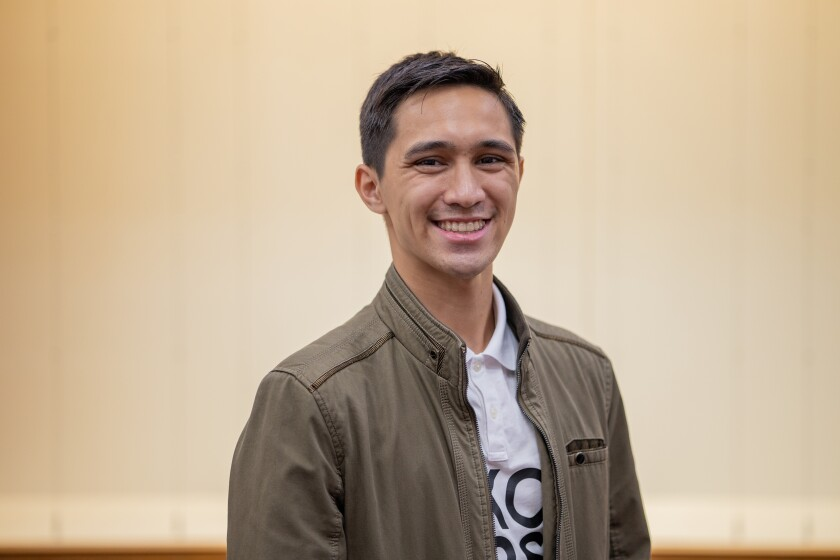 Auahi Aiu smiles wearing a green jacket and white and black shirt with an off-white background behind him.