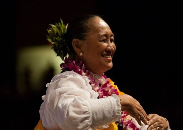 Aunty Kela smiles as she's performing the hula in a white shirt with leis and black background.