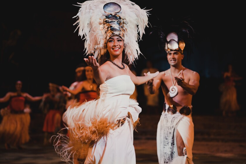Tetuaapua smiling wearing a white shirtless dress with a feathered Tahitian dance clothing around her waist and a white feathered tall head ornament with mother of pearl on her head and other dancers behind her.