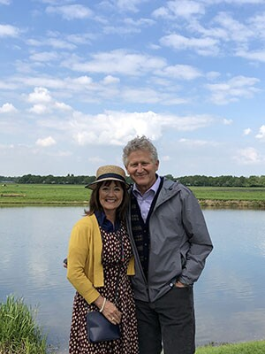 Fred Woods and his wife, JoAnna, standing in front of a lake