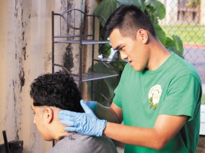 A man gives another man a haircut outdoors.