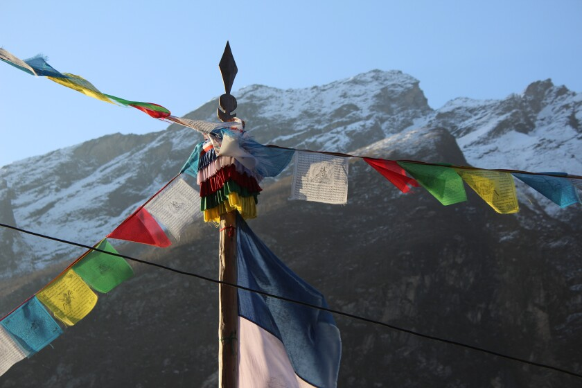 A photo of colored banners with a mountain in the background.