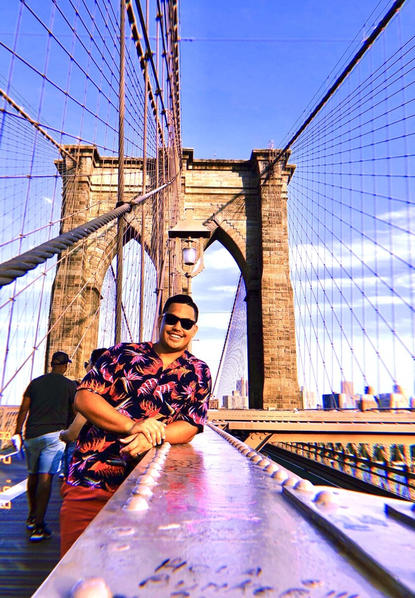 Ly stands on the Brooklyn Bridge.