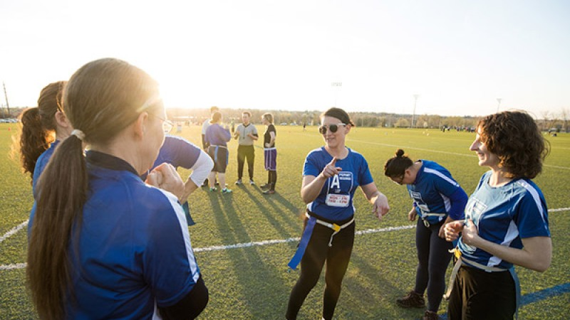 Three faculty members talk on the sideline during their flag football game