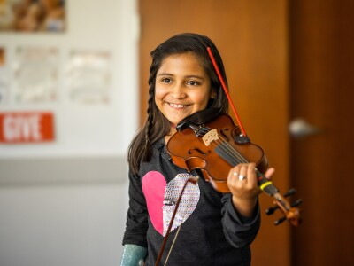Adia Cardona, young violinist, stands with her violin