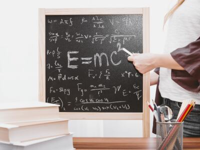 image of a female standing next to a blackboard with the math equations on it