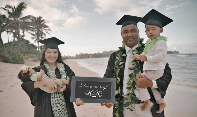 "Serena (left) holds a baby wearing green in one arm while holding a sign with Justin that says ""Class of 2020"" while Justin (right) holds his son with a leaf lei on. They're both wearing graduation caps and gowns and their son is wearing a cap."