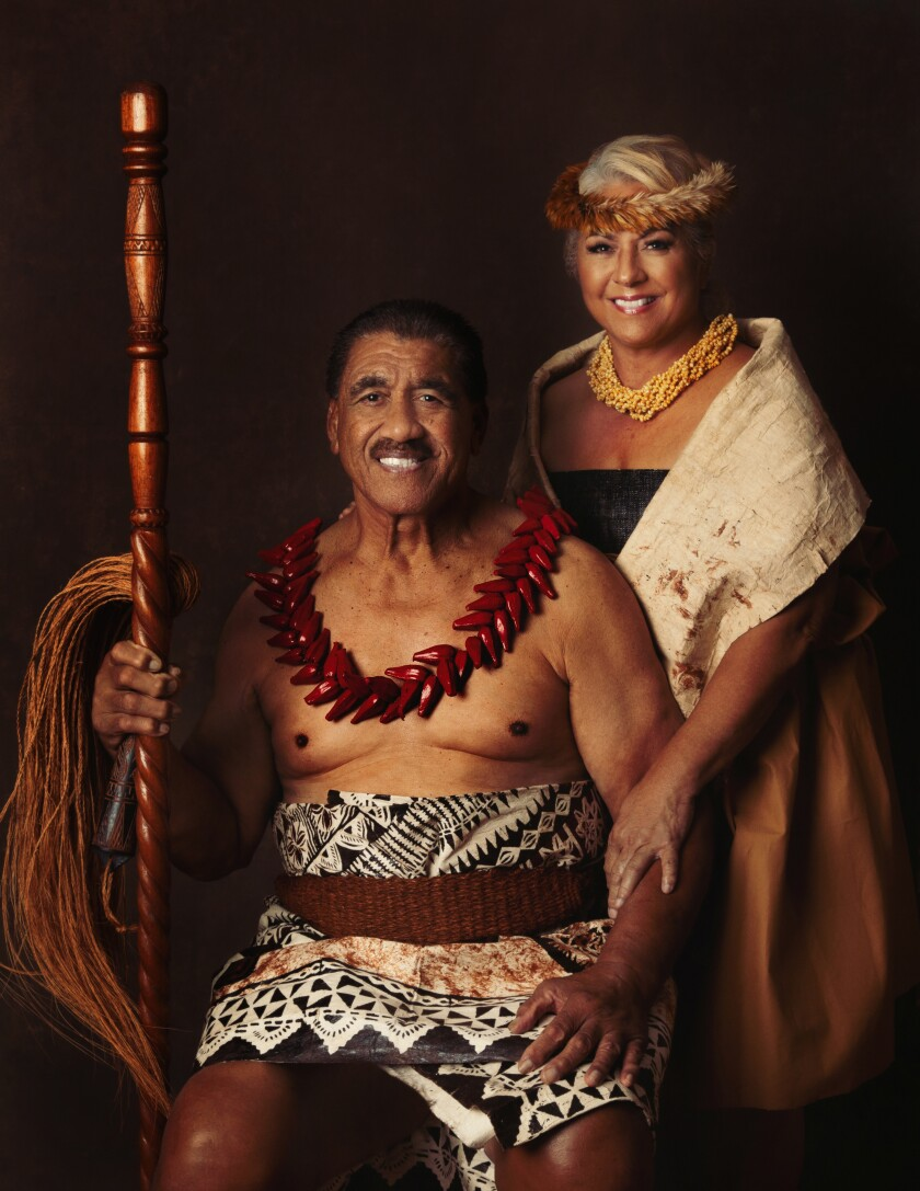 Junior and Almira Ah You pose in traditional Polynesian clothing with black background.